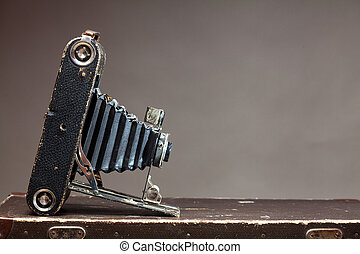 Old vintage camera lying on suitcase on gray background