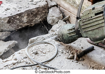 Builder worker with pneumatic hammer drill - close up...