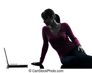 woman serious computing laptop computer silhouette