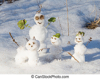 Three funny snowmen and snow cat standing on a brilliant...