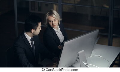 Managing Issues - Close up of two coworkers computing in the...