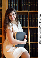 A young woman in the library - A happy young woman is...