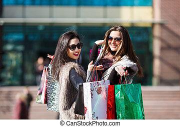 Shopping women outdoors - Young beautiful women holding...