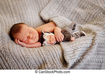 newborn baby sleeping on fur bed - on a bed in a knitted...