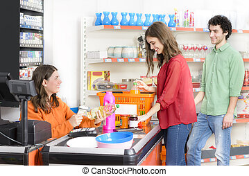 Customers in line at checkout - People in a market at...