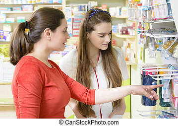 Customer in a drugstore - Young female pharmacist having a...