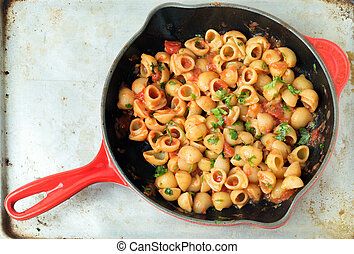 Arrabiata pasta in a pan - Gomiti elbow pasta shells in...