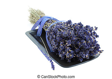 dry lavender bunch with blue strip on a black square plate...
