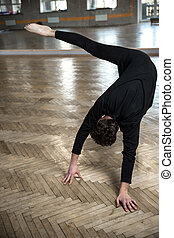 Young male dancer stretching at gym