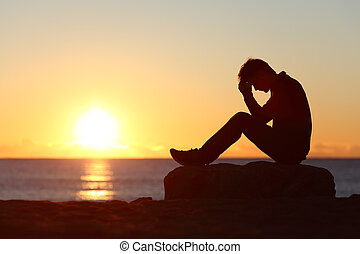 Sad man silhouette worried on the beach at sunset with the...