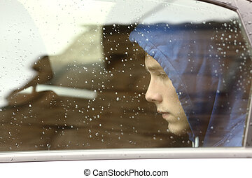 Sad teenager boy worried inside a car looking through the...