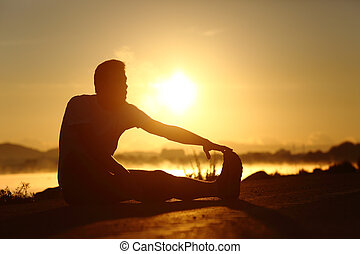 Silhouette of a fitness man stretching at sunset