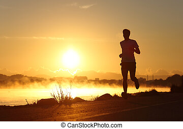 Silhouette of a man running at sunrise with the sun in the...