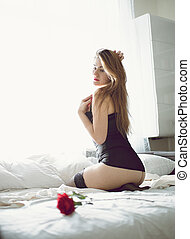 Photo of from back of sexy woman in lingerie sitting on bed...