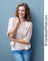 Cheerful mid adult woman smiling in jeans and sweater -...