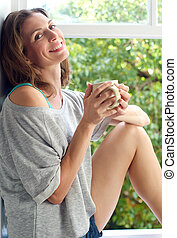 Attractive woman sitting by window at home with cup of...