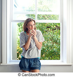 Healthy woman standing by window at home with cup of coffee...