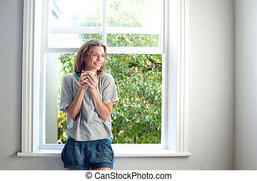 Happy woman standing by window smiling with cup of coffee -...