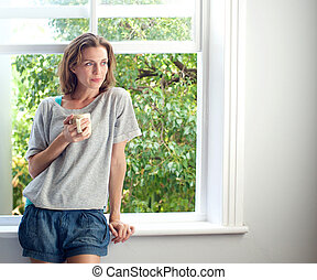 Woman standing by window at home with cup of coffee -...