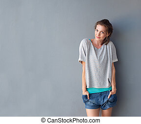 Happy cute mid adult woman standing against gray background...