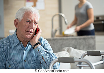 Senior talking on the phone and granddaughter washing dishes