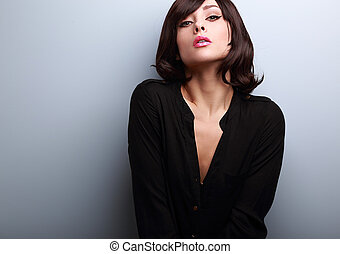Sexy short hair female model posing in black shirt on blue...