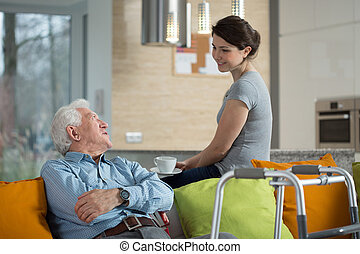 Grandfather talking with loved granddaughter in his home