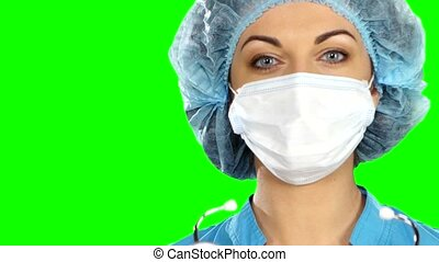 A female doctor with a stethoscope listening, isolated on green screen.