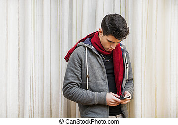 Young man standing indoor typing a text message on his phone