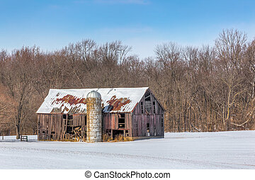 Snowy Old Barn and Silo - An old and dilapidated barn and...