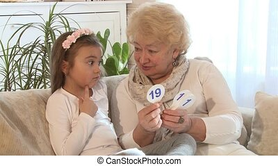 Little girl learning math at home - Grandmother showing...