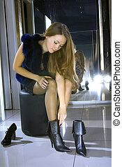 woman fits on a boots in a boutique