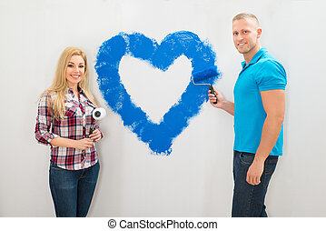 Couple Painting Heart On Wall
