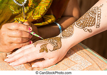 henna painting - woman getting a henna painting on her hand