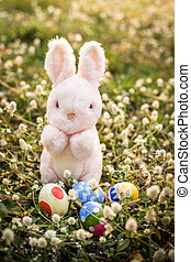 Sugar rabbit and easter eggs on meadow.