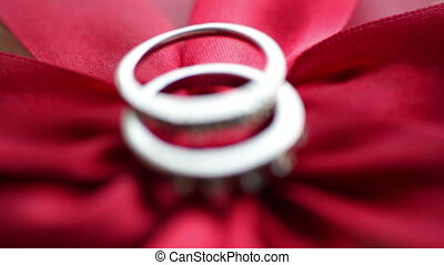 Two rings lie on a red bow.
