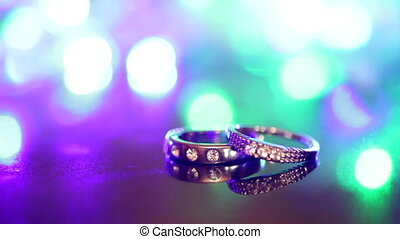 Two rings are on the table at the flashing multicolored...