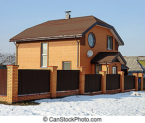 Modern two-storey red brick cottage in early spring