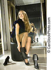 girl fits on a boots in a boutique