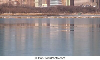 Chicago skyline reflecting on ice - Chicago, Illinois...