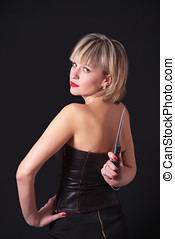Model with large knife behind her back - A blond model with...