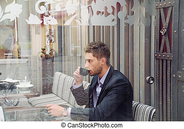 young attractive businessman drinking espresso coffee in the...