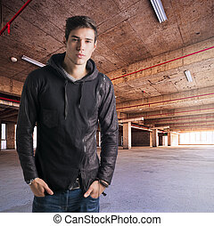 Trendy attractive young man standing in empty warehouse or...