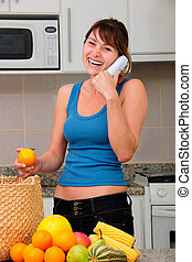woman talking on phone while unpacking groceries