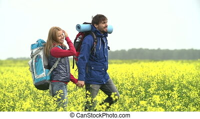 Tourists in Yellow Meadow - Tracking shot of couple of...