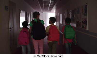 Back to School - Shaky camera following four pupils passing...