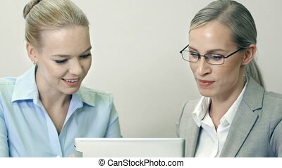 Project Management - Close up of female colleagues seated at...