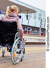 woman sitting in a wheelchair at a train station - a young...