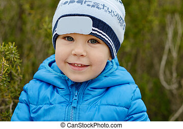 happy toddler boy outdoors wearing blue jacket