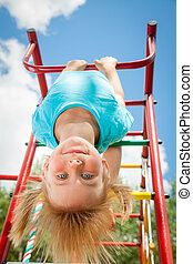 Happy child on a jungle gym - Low angle view of cute blond...